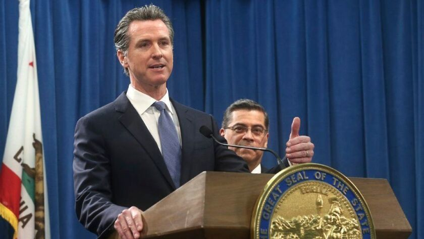 California Gov. Gavin Newsom, with Atty. Gen. Xavier Becerra, answers a question concerning a lawsuit the state plans to file against President Trump over his declaration of a national emergency at the border.