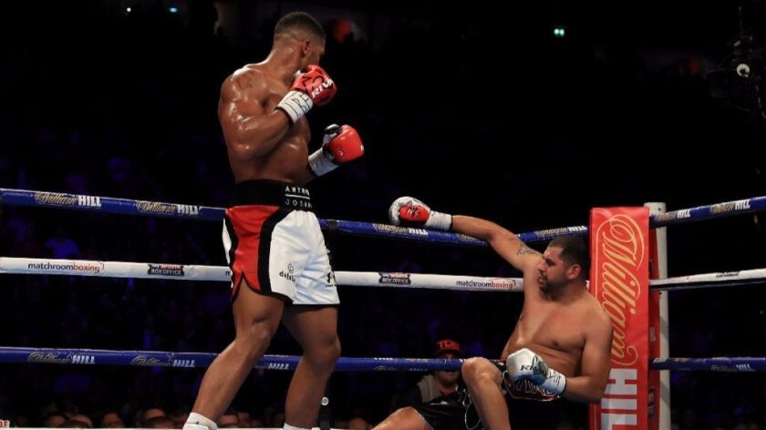 Anthony Joshua knocks down Eric Molina during their IBF world heavyweight championship fight on Dec. 10 in Manchester, England.