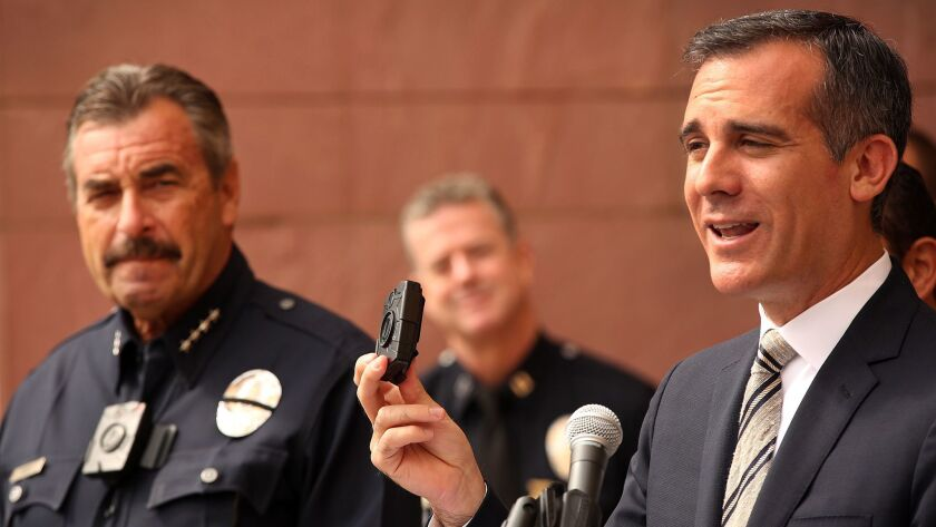Mayor Eric Garcetti, right, shows off a police body camera at a 2015 news conference with LAPD Chief Charlie Beck. Thousands of L.A. police officers now wear the devices.