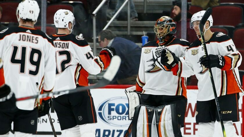 Ducks goaltender Ryan Miller, second from right, celebrates the team's 3-1 win against the Arizona Coyotes with teammates as time expires on Tuesday in Glendale, Ariz.
