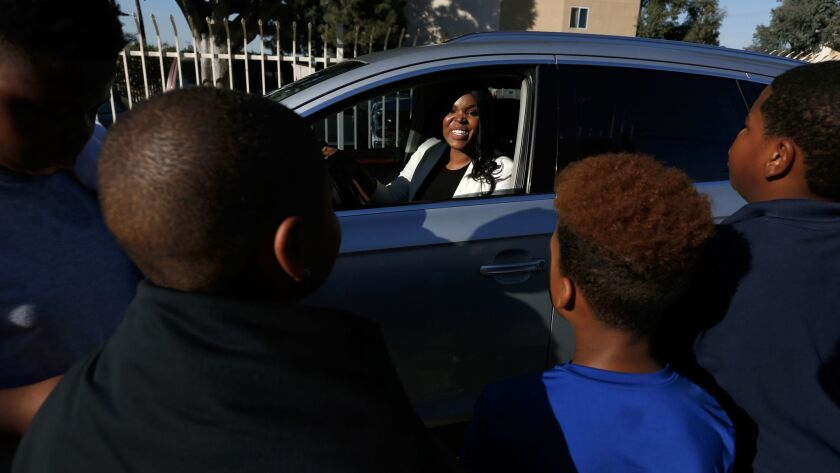 Compton Mayor Aja Brown greets neighborhood children outside of the Center for Sustainable Communities under construction in Compton.