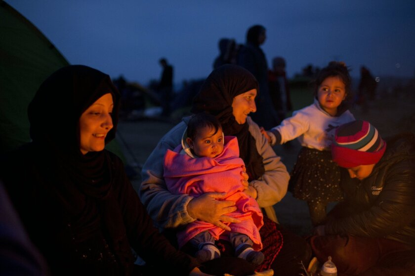 Syrian refugees warm themselves near a makeshift fire after they arrived at the Greek border station of Idomeni on Friday, Feb. 26, 2016. About 4000 refugees are stranded at the Greek Macedonian- border, authorities said. (AP Photo/Petros Giannakouris)