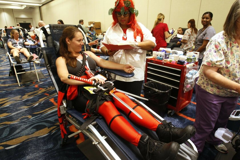 Ophelia Hsu, from Albuquerque, N.N., dressed a Lady Deadpool, is a regular blood donor and decided to give at Comic-Con. Denise Green, a phlebotomist with the Blood Bank, was dressed as Wonder Woman disguised as Poison Ivy.