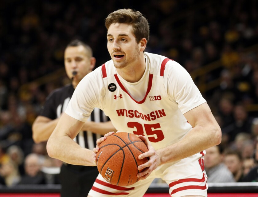 FILE - In this Jan. 27, 2020, file photo, Wisconsin forward Nate Reuvers looks to pass during the first half of an NCAA college basketball game against Iowa in Iowa City, Iowa. Wisconsin begins this pandemic-delayed season with most of the same players who created so many memorable moments during a magical stretch drive last year. (AP Photo/Charlie Neibergall, File)