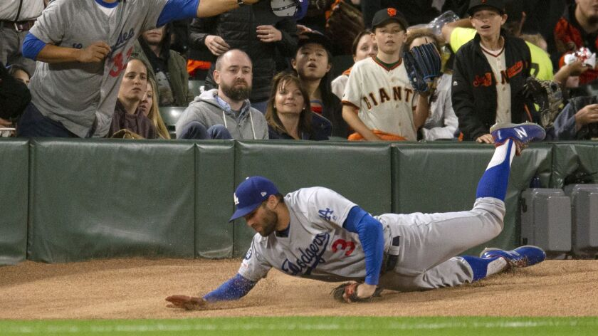 Los Angeles Dodgers left fielder Chris Taylor trips over the bullpen pitcher's mound while chasing a