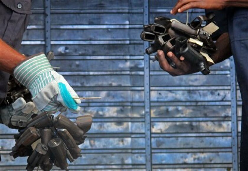 Police officers carry seized handguns, zip-tied into bundles, to a waiting truck at the police armory, in Kingston, Jamaica, Tuesday Feb. 7, 2012. Roughly 2,000 seized guns were transported to a local cement factory and melted down by police and UN officials. (AP Photo/ David McFadden)
