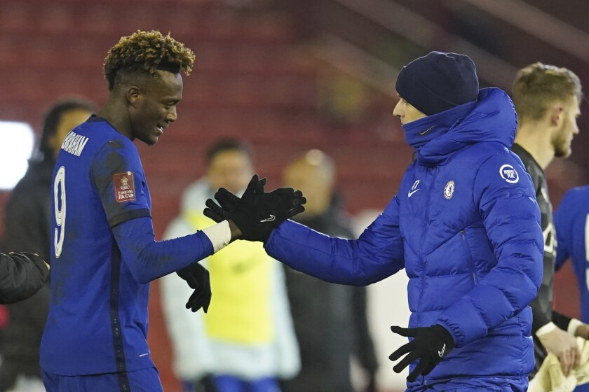 Chelsea's head coach Thomas Tuchel, right shakes hands with match winner Chelsea's Tammy Abraham at the end of the English FA Cup fifth round soccer match between Barnsley and Chelsea at the Oakwell Stadium in Barnsley, England,Thursday Feb. 11, 2021. (AP Photo/Dave Thompson, Pool)