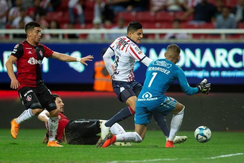 El jugador de Chivas, Ronaldo Cisneros (c) disputa el balón con el Esteban Carvajal (i) y el guardameta José Hernández (d) de Atlas durante el juego correspondiente a la jornada 7 del torneo mexicano de fútbol, celebrado en el estadio Akron, en la ciudad de Guadalajara (México). EFE/Archivo
