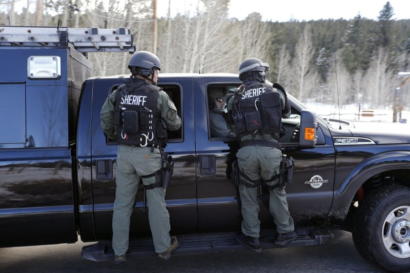Jefferson County SWAT officers work at the scene where a man opened fire on sheriff's deputies before the officers returned fire, killing the man, outside Bailey, Colo., Wednesday, Feb. 24, 2016. Authorities say the man, who lost ownership of his home two years ago, opened fire on the officers trying to serve an eviction notice. (AP Photo/Brennan Linsley)