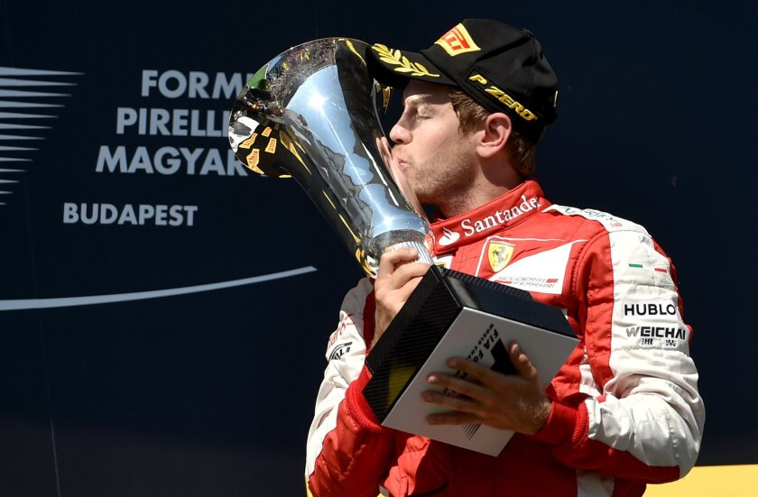 TOPSHOTS Ferrari's German driver Sebastian Vettel kisses the trophy as he celebrates on the podium winning the Hungarian Formula One Grand Prix at the Hungaroring circuit near Budapest on July 26, 2015. AFP PHOTO / ANDREJ ISAKOVICANDREJ ISAKOVIC/AFP/Getty Images ** OUTS - ELSENT, FPG - OUTS * NM, PH, VA if sourced by CT, LA or MoD **