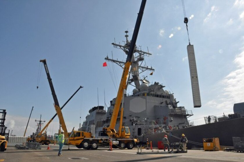 Workers service a destroyer at the Seal Beach Naval Weapons Station, 80 miles north of San Diego