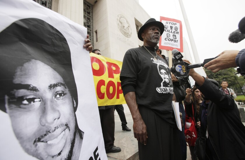 Cephus Johnson stands next to a poster of his nephew Oscar Grant during a protest outside a Los Angeles courthouse in 2011.
