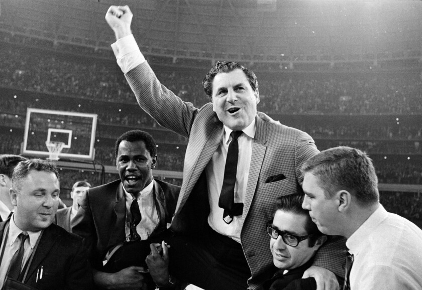 A 1968 photo shows Houston basketball coach Guy V. Lewis being carried to the dressing room after the Cougars' upset win over UCLA at the Astrodome in Houston.