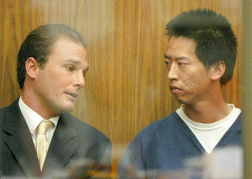 Bryan Chenhua Chang, right, talks with public defender Jeremy Burland in the glass-enclosed section of the Vista Superior Court during his hearing Friday.