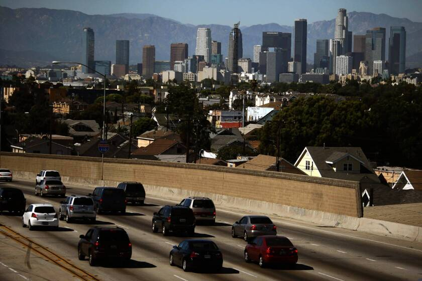 On a clear day in downtown Los Angeles, traffic travels north on the 110 Freeway. Despite a threefold increase in people and cars in the last 50 years, California's strict vehicle emissions standards have managed to significantly clear the state's air, according to new research.