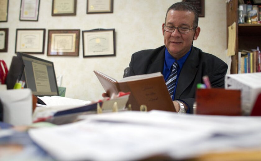 Pastor and former Bell councilman Luis Artiga looks over a diary he kept during the corruption trial in his office at Bell Community Church.