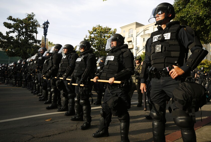 San Diego police officers look on during a youth-led protest near San Diego Police headquarters on June 1, 2020.