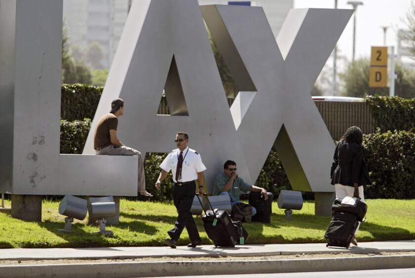 Travelers sit on the LAX Los Angeles International Airport sign.