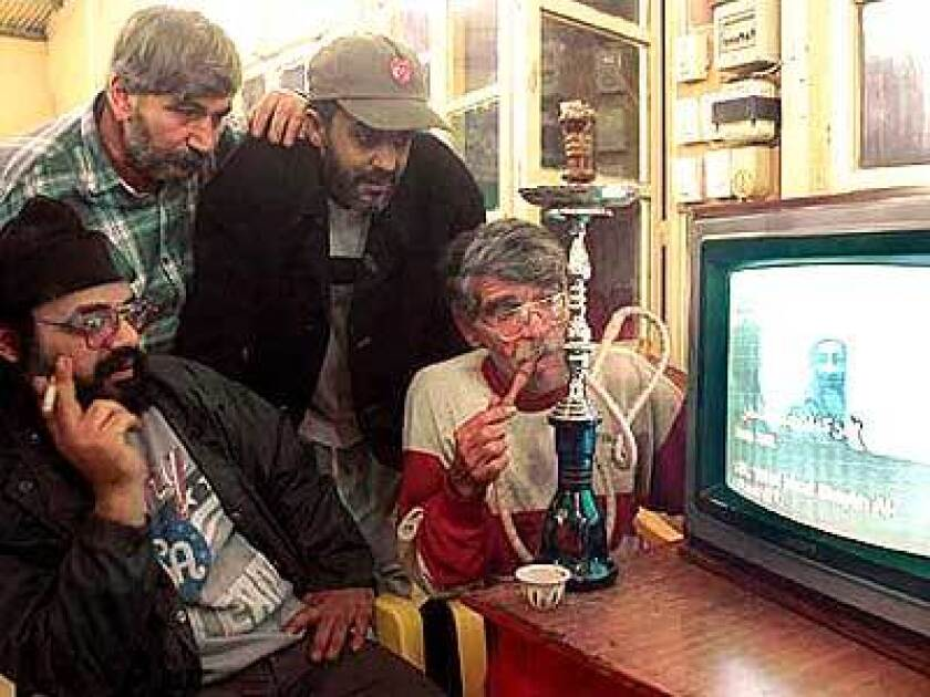 Lebanese men watch the broadcast.