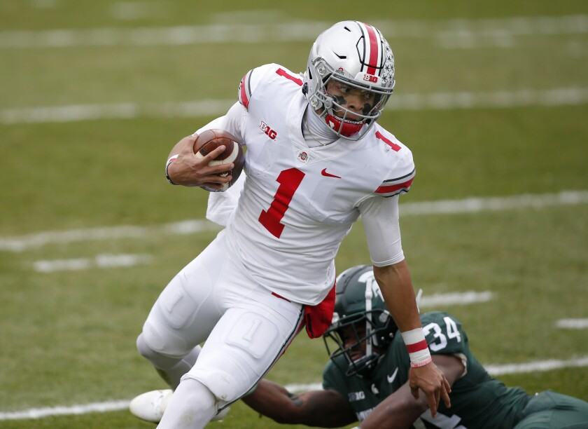 Ohio State quarterback Justin Fields (1) escapes from Michigan State linebacker Antjuan Simmons during the first half of an NCAA college football game, Saturday, Dec. 5, 2020, in East Lansing, Mich. (AP Photo/Al Goldis)