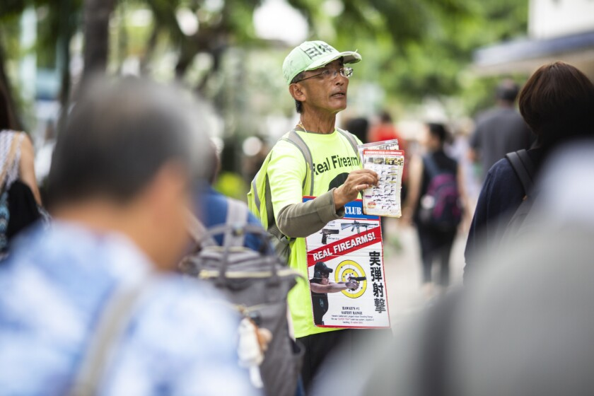 HONOLULU, HI - AUGUST 26: A leaflet distributor for The Waikiki Gun Club hands out flyers advertisin