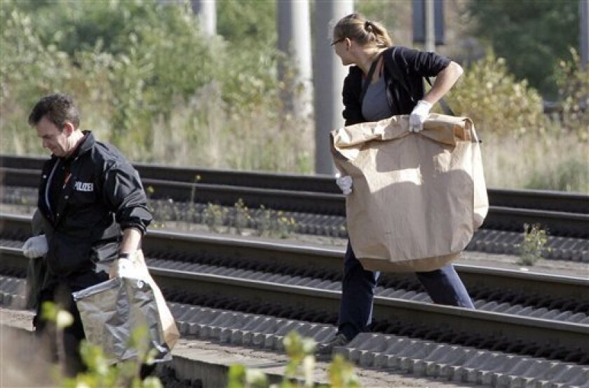 Police officers carry away paper bags with suspected explosive devices at the rail tracks nearby the Staaken station in Berlin, Germany, Wednesday, Oct. 12, 2011. Three more arson attacks have targeted Berlin's railway network, police said Wednesday. Two of the attacks were thwarted, while a third device caught fire but caused no injuries. It brings the total of attempted arson attacks in and around Germany's capital to six since Monday.(AP Photo/Michael Sohn)