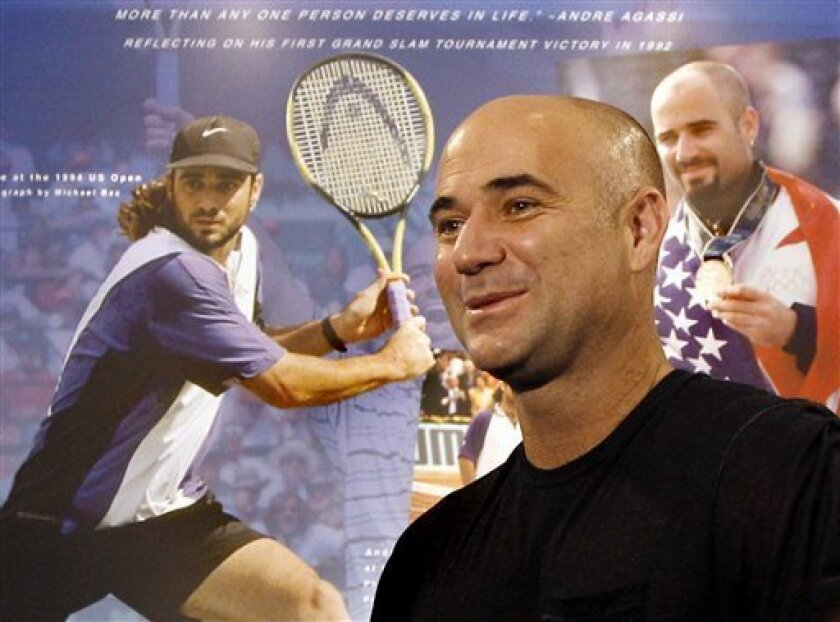 Tennis great Andre Agassi reacts as he looks at an exhibit dedicated to him at the International Tennis Hall of Fame, Friday, July 8, 2011, in Newport, R.I. Agassi will be inducted into the Hall of Fame on Saturday. (AP Photo/Elise Amendola)