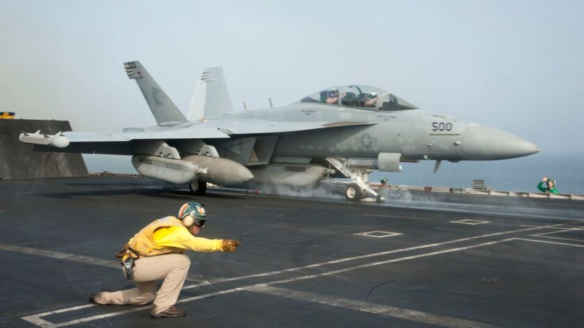 131012-N-RY581-029 GULF OF OMAN (Oct. 12, 2013) Lt. Thomas McDonald directs an EA-18G Growler assig