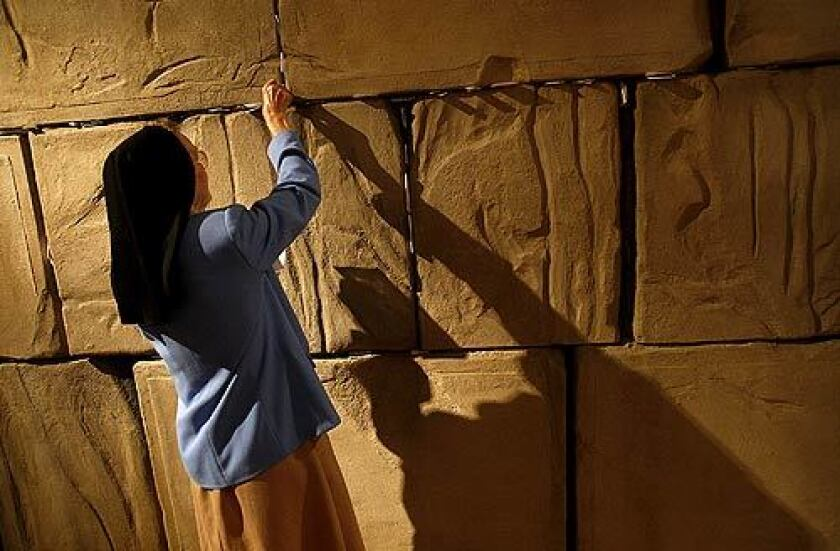 Sister Thomas Bernard MacConnell of the Spirituality Center at Mount St. Mary's College tucks a note into a replica of Jerusalem's Western Wall, which is part of an exhibit at the Skirball Cultural Center in Los Angeles that highlights Pope John Paul II's relationship with Jews.