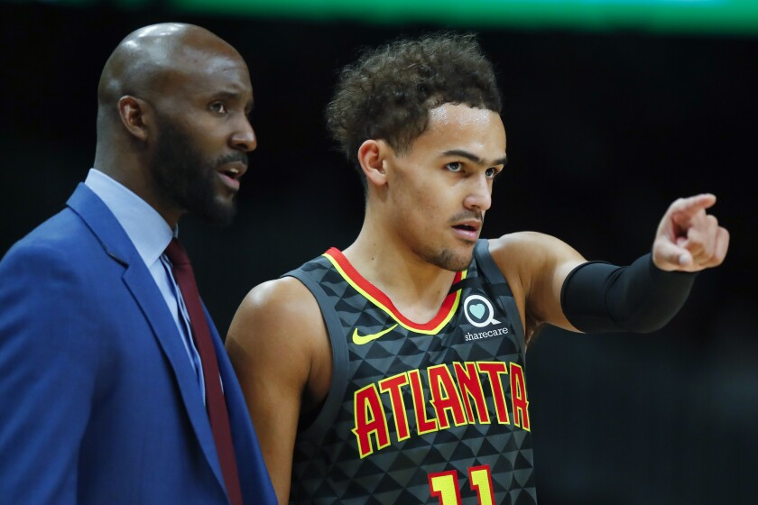 Atlanta Hawks guard Trae Young (11) reacts with head coach Lloyd Pierce in the first half of an NBA basketball game against the New York Knicks on Sunday, Feb. 9, 2020, in Atlanta. (AP Photo/Todd Kirkland)