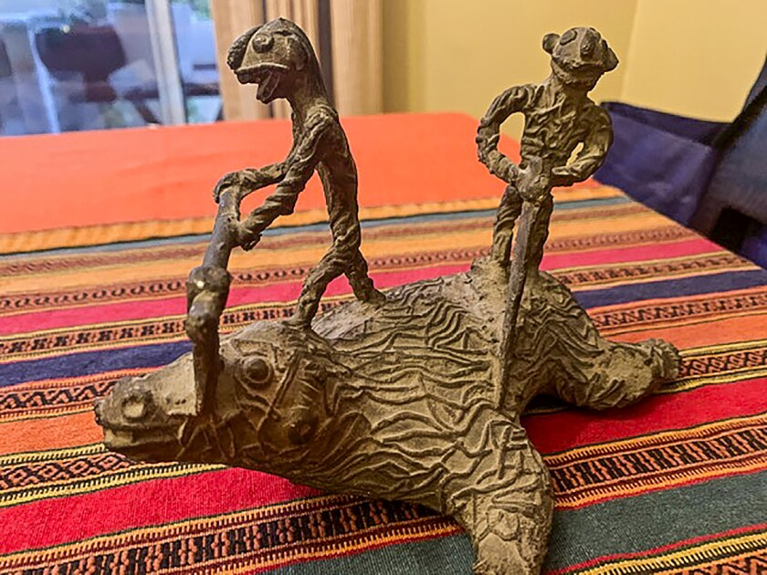 A statuette of a beast being butchered on a striped orange blanket in India. The buyer of this remembrance from India still doesn't understand its meaning.