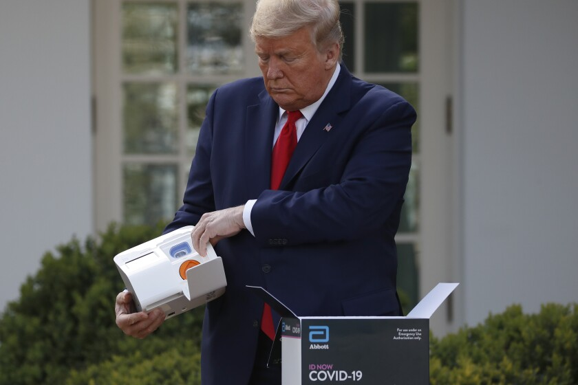 President Trump opens a box containing a five-minute test for COVID-19 from Abbott Laboratories in the Rose Garden of the White House on Monday.