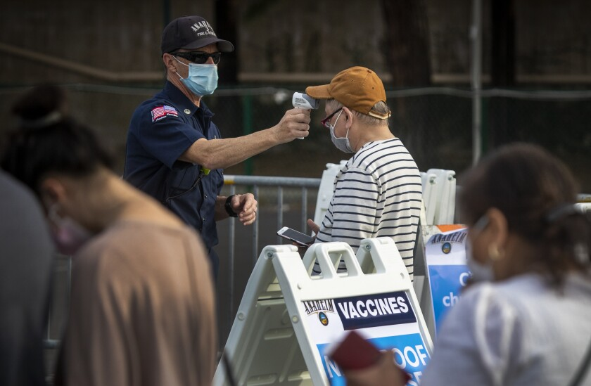 A man's temperature is checked at the Disneyland COVID-19 vaccination site in January.