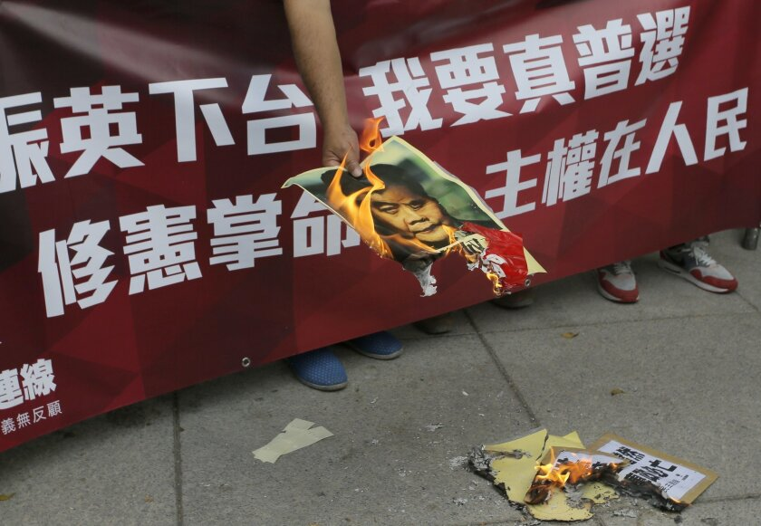 """A protester burns a picture of Hong Kong's Chief Executive Leung Chun-ying during a protest outside a flag raising ceremony venue to mark the 18th anniversary of Hong Kong's handover to China in Hong Kong, Wednesday, July 1, 2015. The banner reads """" I want universal suffrage and Leung Chun-ying ste"""