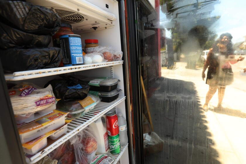 Artist Mary A. Harris, is seen through a refrigerator door, that contains donated food at Little Amsterdam Coffee shop.