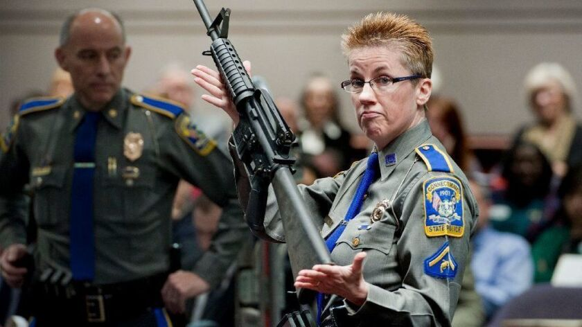A Connecticut State Police detective holds a Bushmaster AR-15-style rifle, the same make and model used in the 2012 Newtown school shooting.