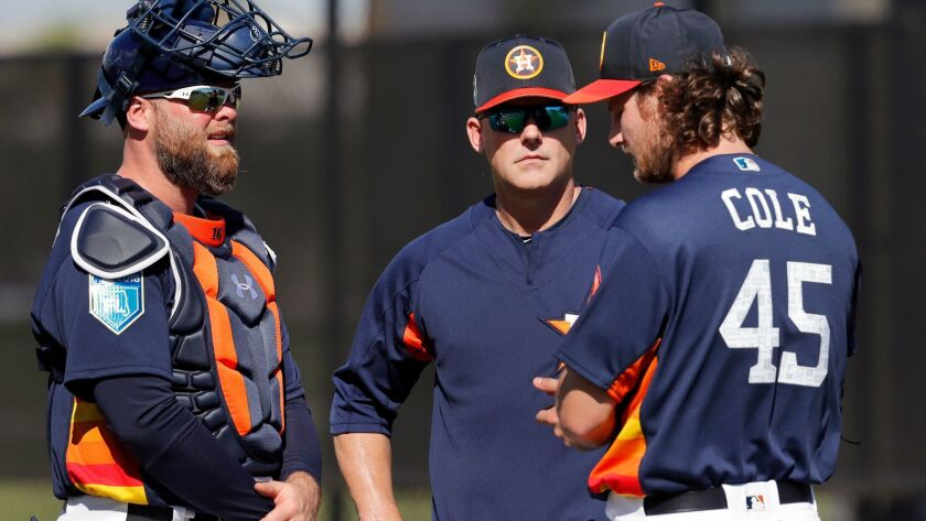 Astros pitcher Gerrit Cole (45) talks with manager A.J. Hinch and catcher Brian McCann, left, after throwing a bullpen session during spring training baseball practice Thursday, Feb. 15, 2018, in West Palm Beach, Fla.