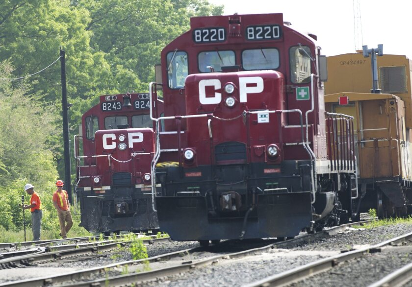 FILE - In this May 23, 2012, file photo, surveyors work next to Canadian Pacific Rail trains parked on the tracks in Toronto. As deal talks begin, Canadian National railroad says on Monday, April 26, 2021 it is receiving broad support for its $33.7 billion bid to buy Kansas City Southern. (Nathan Denette/The Canadian Press via AP, File)