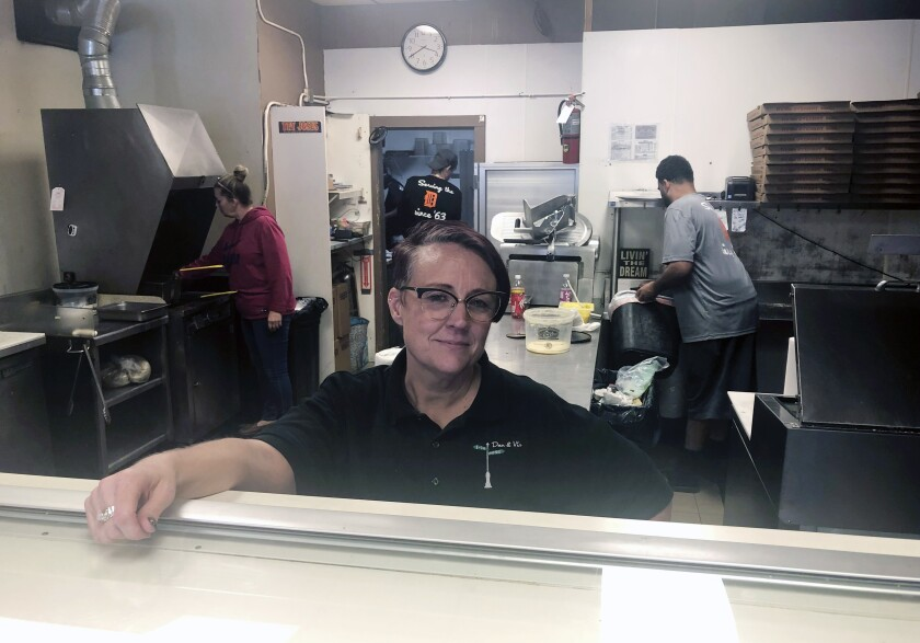 """Tina Wheeler, manager of Dan and Vi's pizza poses for a photo, Thursday, Oct. 10, 2019 in Detroit. Dan and Vi's pizza deli, one of the few eateries near the Detroit-Hamtramck General Motors plant, says sales have been down, though Wednesday's noontime crowd snaked around the small shop nearly to the door. """"We're definitely noticing a difference in sales, but we're gonna be OK,"""" said manager Tina Wheeler. """"We've been in the neighborhood 56 years. We're not going anywhere."""" (AP Photo/Corey Williams)"""