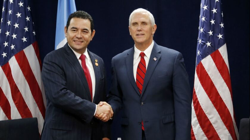 Vice President Mike Pence, right, shakes the hand of Guatemalan President Jimmy Morales during the U.S.-Central America Security Conference in Miami in 2017.