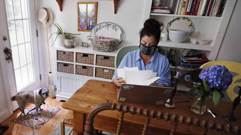 """Poet Tammi Truax looks over her recent work, as her pug """"Pie"""" looks on, while seated at her writing table, wearing a protective mask due to the COVID-19 virus outbreak, Wednesday, July 29, 2020, at her home in Eliot, Maine. Truax, the poet laureate for Portsmouth, N.H., pens a weekly pandemic poem that is included in the city's COVID-19 newsletter. (AP Photo/Charles Krupa)"""