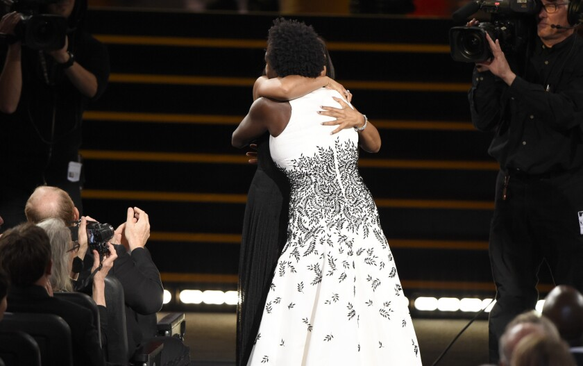 Taraji P. Henson, left, embraces Viola Davis before Davis walks on stage to accept the Emmy award for outstanding lead actress in a drama series.