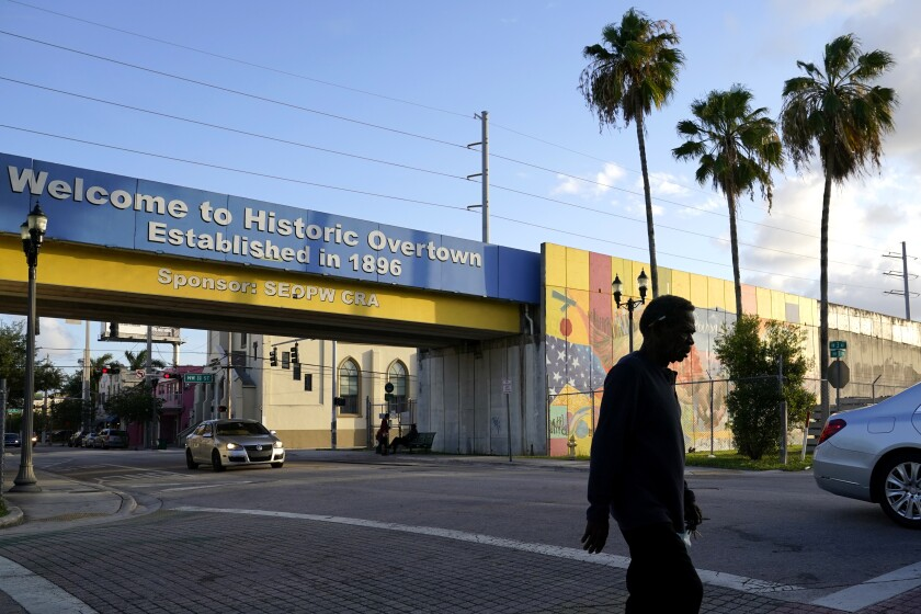 A man walks down a street, Sunday, May 16, 2021, in the Overtown neighborhood in Miami. Miami was one of numerous Black cities across the country where interstate highways were built, disrupting communities. The Signature Bridge project coincides with the revitalization of the neighborhood that is currently underway. (AP Photo/Lynne Sladky)