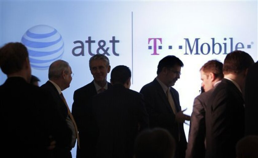 People gather before an AT&T news conference in New York, Monday, March 21, 2011. AT&T Inc. said Sunday it will buy T-Mobile USA from Deutsche Telekom AG in a cash-and-stock deal valued at $39 billion that would make it the largest cellphone company in the U.S. (AP Photo/Richard Drew)