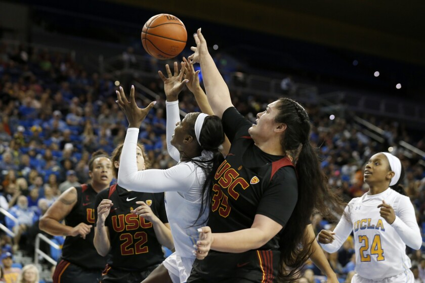 UCLA forward Michaela Onyenwere (21) and USC forward Alissa Pili (35) fight for a lose ball during a game at Pauley Pavilion on Dec. 29.