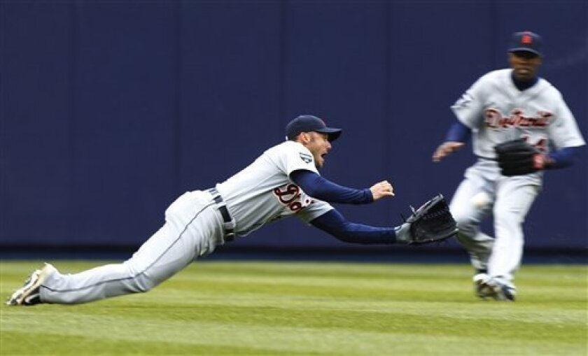 Detroit Tigers left fielder Ryan Raburn dives to catch a ball hit by New York Yankees' Russell Martin (55) as teammate Austin Jackson (14) looks on during the fifth inning of a baseball game against the New York Yankees Thursday, March 31, 2011, at Yankee Stadium in New York. (AP Photo/Frank Frankl