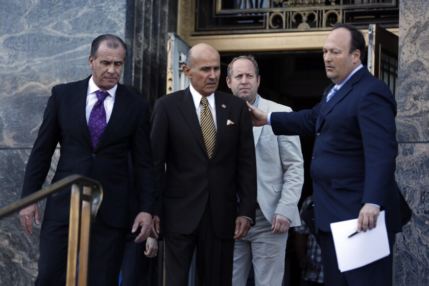 Retired Los Angeles County Sheriff Lee Baca, center, leaves the federal courthouse in downtown Los Angeles after pleading guilty Wednesday to lying to federal investigators.