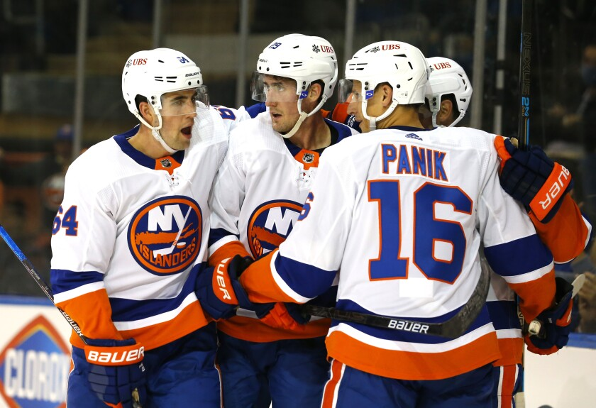 New York Islanders center Brock Nelson (29) celebrates with teammates Erik Gustafsson (64) and Richard Panik (16) after scoring a goal against the New York Rangers during the first period of a preseason NHL hockey game, Sunday, Sept. 26, 2021, in New York. (AP Photo/Noah K. Murray)