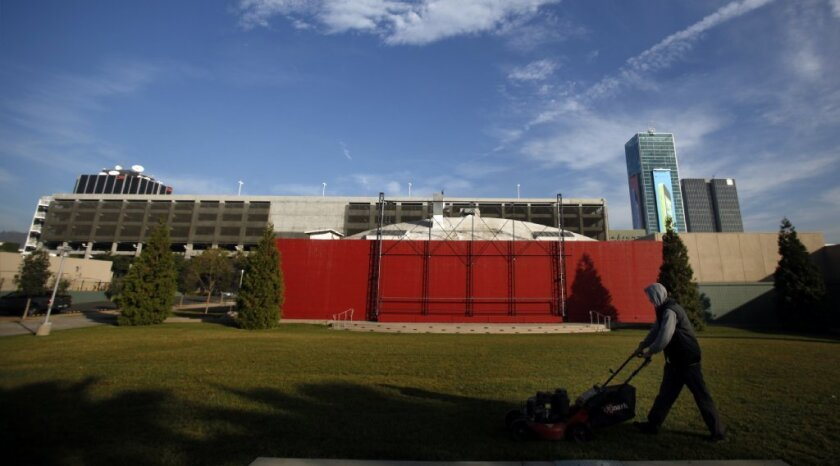 A worker cuts the grass at the Hollywood property that the Academy of Motion Picture Arts and Sciences sold in January after deciding not to build a $400-million movie museum there. Instead, the academy is planning to open a museum on the Los Angeles County Museum of Art campus.