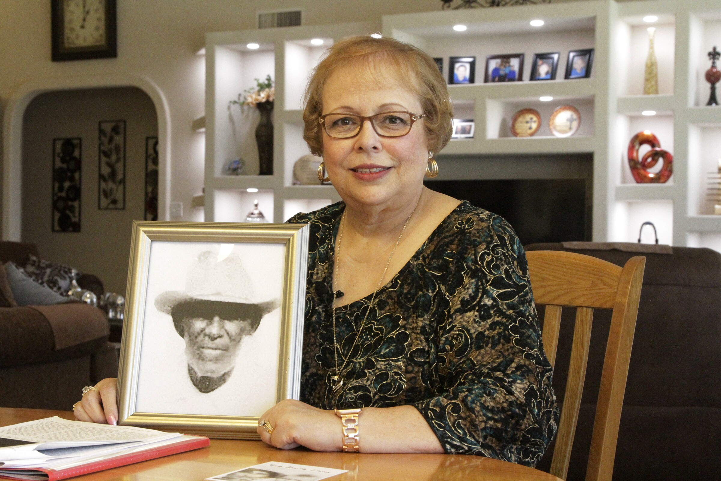 Arlinda Valencia with a portrait of her great-grandfather Longino Flores